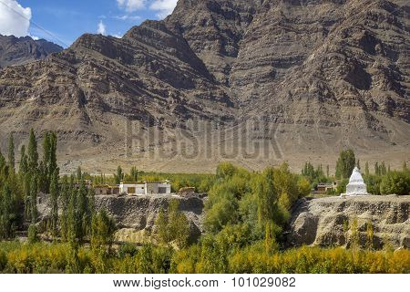 Scenic view of Tibetan house and stupa and sand mountain background Ladakh ,India.
