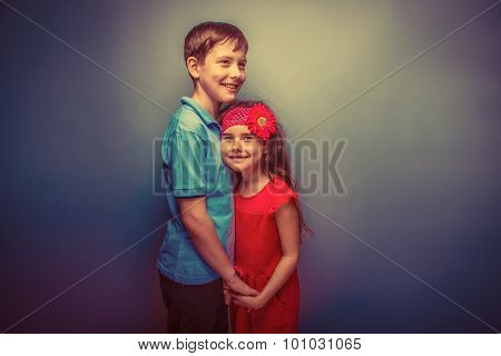 tween girl holding hands teenage boy on a  gray  background retro