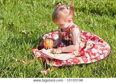 Girl Eating An Apple And Looking Book On The Grass