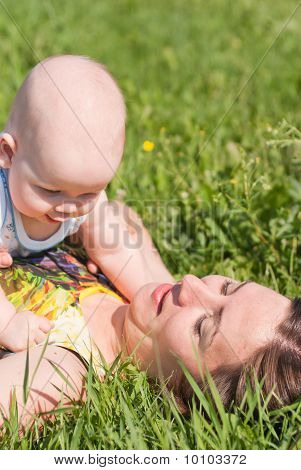 Mom And Baby Lie On The Grass, Play