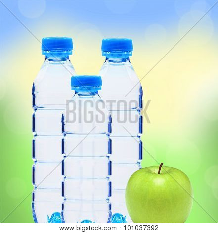 Blue Bottles With Water And Green Apple Over Blurred Nature Background