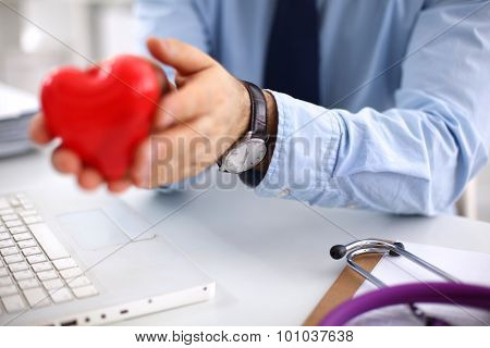 Young doctor holding a red heart, in office