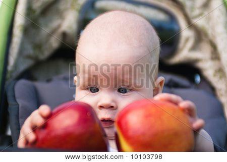 kleines Kind mit beiden Händen zwei Äpfel