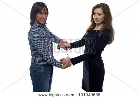 Young man and woman with pair of handcuffs