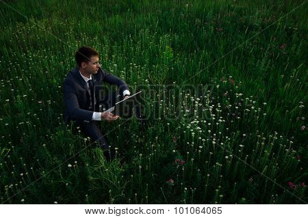Buisnessman With Laptop Sit On The Grass