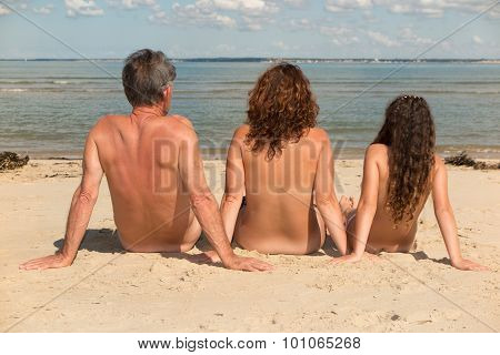 Naked Family Sitting On The Beach.
