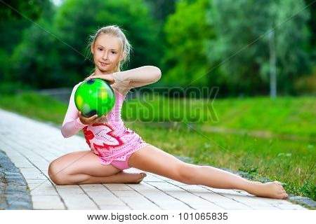outdoor portrait of young cute little girl gymnast training with ball in park