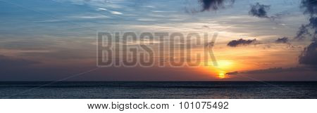 Setting sun over ocean horizon panorama