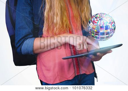 Student using tablet in library against sphere made of flags