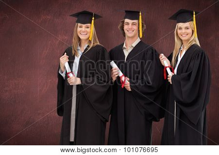 Three smiling students in graduate robe holding a diploma against desk