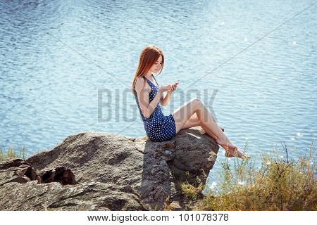 Woman sitting on the cliff
