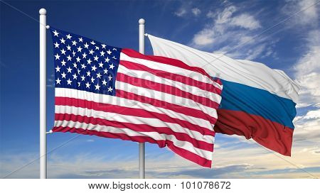 Waving flags of USA and Russia on flagpole, on blue sky background.