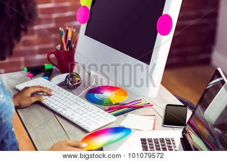 Female graphic designer working at desk against red brick background