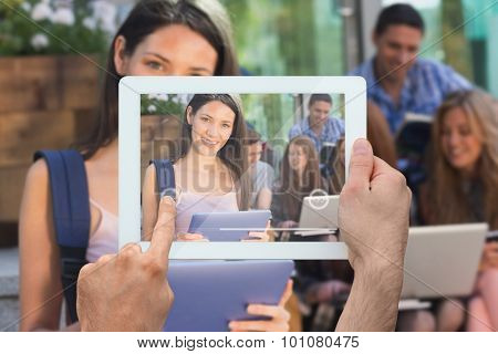 Hand holding tablet pc against pretty student using her tablet pc on campus