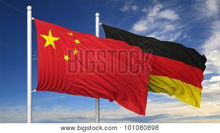 Waving flags of China and Germany on flagpole, on blue sky background.
