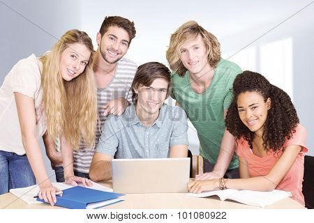 College students using laptop in library against modern hallway