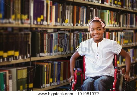 Girl sitting in wheelchair in school corridor against close up of a bookshelf