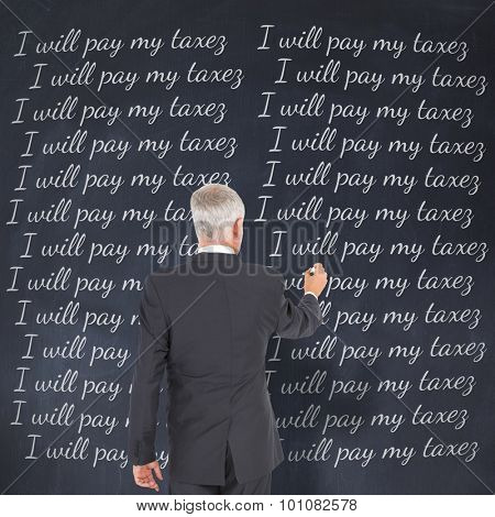 Rear view of businessman standing and writing against black background