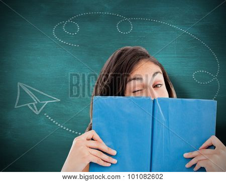 Portrait of a student winking behind a blue book against green chalkboard