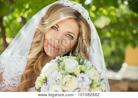 Beautiful Bride With Wedding Bouquet Of Flowers Outdoors In Green Park.