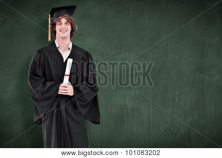 Smiling student in graduate robe against green chalkboard