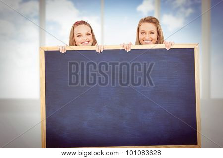 Close up of young women behind a blank sign against bright white room with windows