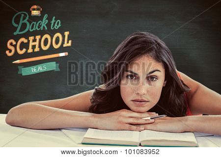 Frowning student head on her books against green chalkboard
