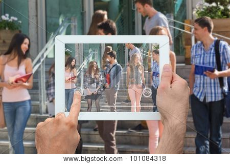 Hand holding tablet pc against happy students walking and chatting outside