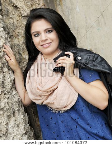 A pretty teen girl happily leaning against a crumbling rock wall.