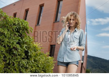 Young confident business woman walking in hurry, talking on mobile phone on the city street