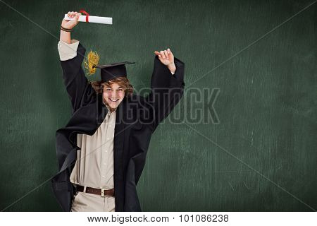 Male student in graduate robe jumping against green chalkboard