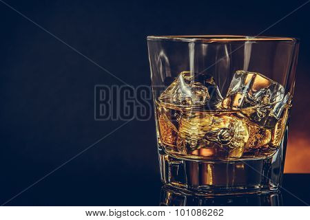 Glass Of Whiskey On Black Background With Reflection, Warm Atmosphere