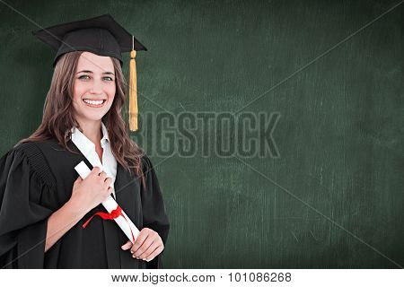 A smiling woman with a degree in hand as she looks at the camera against green chalkboard