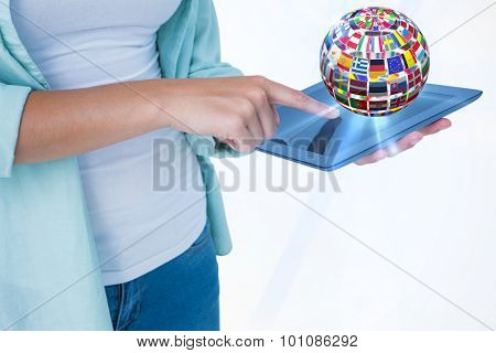 Woman using tablet pc against sphere made of flags