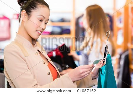 Asian and Caucasian Woman shopping in boutique or fashion store choosing clothes
