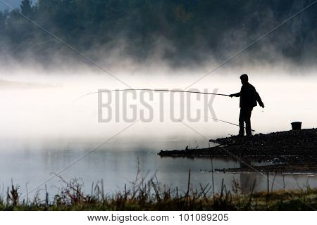 Man Fishing At River Shore
