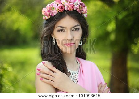 Brunette Girl With Flower Chaplet In Green Filed Wearing In Pink Dress On Green Field.