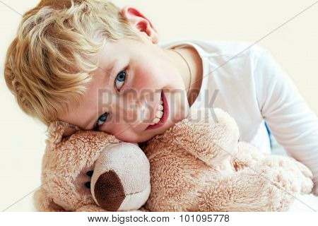 Cute Little Boy Hugs His Teddy Bear. The Manifestation Of Feelings: Of Tenderness And Care.