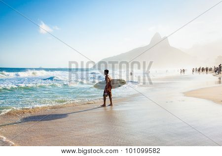 RIO DE JANEIRO, BRAZIL - APRIL 24, 2015: Brazilian surfer walking with surfboard toward Two Brothers Mountain at Ipanema Beach on April 24, 2015 at Copacabana Beach, Rio de Janeiro. Brazil.