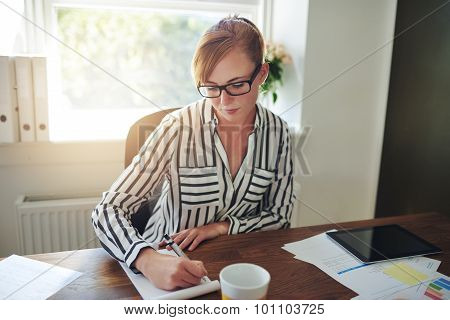 Businesswoman Taking Notes On A Phone Call