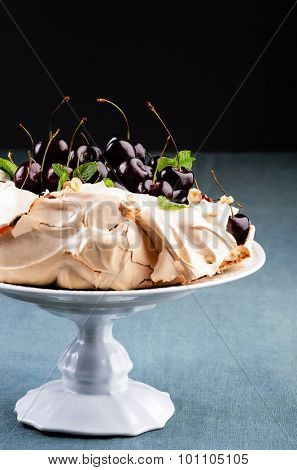 Close up on cherry pavlova on a cake stand, traditionally Australian dessert similar to a meringue with a crisp exterior shell with a marshmallow interior