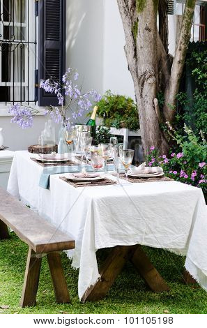 Simple rustic country style table setting for a party gathering in a casual outdoor garden setting