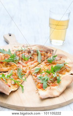 Fresh handmade thin crust pizza with rocket, roasted tomatoes and caramelised onion