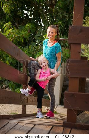 Happy Young Mother And Daughter Standing On Wood Bridge At Beach