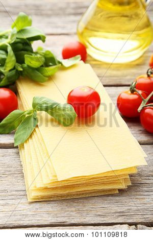 Lasagna, Basil And Tomatoes On Grey Wooden Background