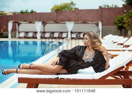 Luxury Resort Sexy Girl Model In Fashion Clothes Relaxing On Beach Bed By Swim Pool. Attractive Blon