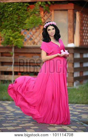 Beautiful Pregnant Woman Holding Baby's Bootee Wearing In Pink Dress In Nature Park Background At Su