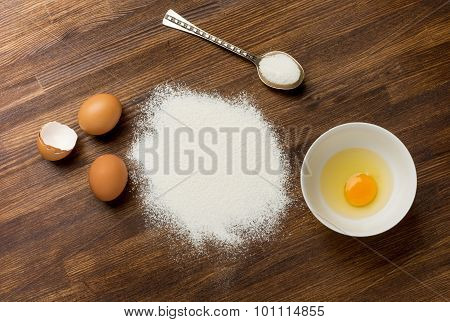 Baking ingredients - flour and eggs on table