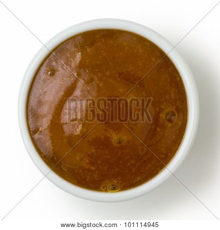 Small White Pot Of Curry Sauce Dip, From Above Isolated On White.