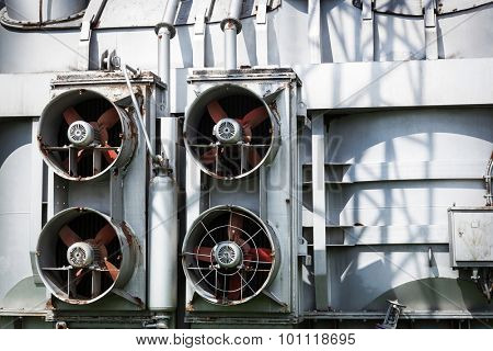 fans outdoors on a metal wall